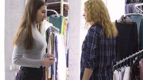 Jeune ouvrière couturière prenant des mesures de client pour travailler les vêtements désirés banque de vidéos