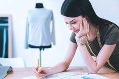 Jeune ouvrière couturière rêvant de son propre atelier de couture image libre de droits