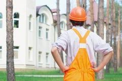 Jeune ouvrier regardant à l'extérieur la construction Photos stock