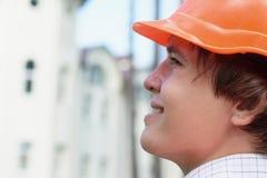 Jeune ouvrier regardant à l'extérieur la construction Images libres de droits