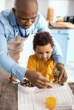 Jeune père agréable jouant avec le dinosaure de jouet ainsi que le fils Photo libre de droits