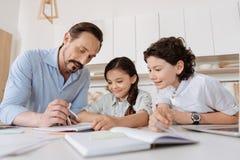 Jeune père aidant ses enfants avec des tâches de maths Images libres de droits