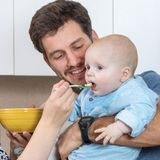 Jeune père appréciant son alimentation de bébé Image stock