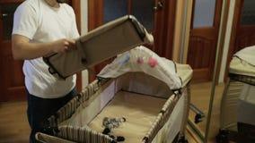 Jeune père assemblant un berceau clips vidéos