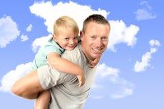 Jeune père attirant et sportif continuant son jeune beau et blond fils arrière ayant la pose d'amusement ensemble d'isolement sur Image stock