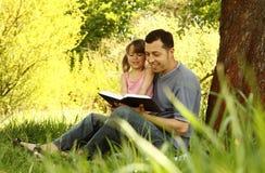 Jeune père avec sa petite fille lisant la bible photos stock