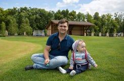 Jeune père avec ses 9 mois de bébé garçon détendant sur l'herbe à Photographie stock libre de droits