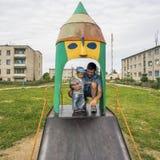 Jeune père avec son fils 1 3 ans sur le terrain de jeu dans le village Images stock