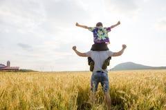 Jeune père avec son petit fils marchant dans le domaine de blé au coucher du soleil dans un jour d'été chaud Photos libres de droits
