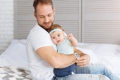 Jeune père barbu étreignant la fille d'enfant en bas âge à la maison Photo libre de droits