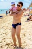Jeune père dans des lunettes de soleil sur la plage avec une petite fille photos stock