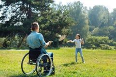 Jeune père dans le fauteuil roulant jouant le badminton avec la fille Photo libre de droits