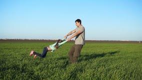 Jeune père dans occasionnel tournant sa fille en cercles, jouant, ayant l'amusement en nature un jour lumineux parenthood banque de vidéos