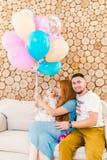 Jeune père de famille, femme et bébé s'asseyant sur le divan à l'intérieur avec le mur décoratif en bois et les ballons multicolo Image libre de droits