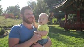 Jeune père de hippie tenant le petit fils en parc banque de vidéos