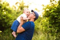 Jeune père en nature tenant le fils de bébé dans les bras Photos stock