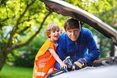 Jeune père enseignant son petit fils à changer l'huile de moteur dans le fami Image stock