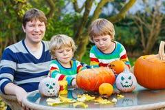 Jeune père et deux enfants de mêmes parents faisant la cric-o-lanterne pour le hallowee Photos stock