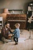 Jeune père et petite fille jouant la guitare acoustique photo stock