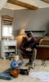 Jeune père et petite fille jouant la guitare acoustique photo libre de droits