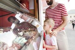 Jeune père et sa crème glacée de achat de petit fils Jour ensoleillé Photo libre de droits