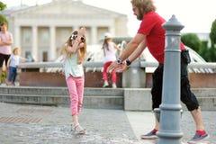 Jeune père et sa petite fille ayant l'amusement avec la fontaine d'eau potable le jour chaud et ensoleillé d'été Image stock
