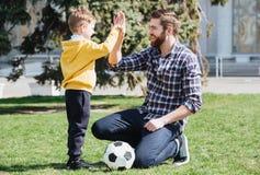 Jeune père et son petit fils donnant la haute cinq Photo stock
