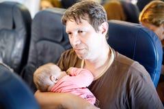 Jeune père fatigué et sa fille de sommeil de bébé pendant le vol sur l'avion partant en vacances Image libre de droits