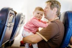 Jeune père fatigué et sa fille pleurante de bébé pendant le vol sur l'avion partant en vacances Photos stock