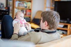 Jeune père fier heureux avec la fille nouveau-née de bébé, portrait de famille ensemble Image stock