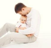 Jeune père heureux embrassant le bébé sur le fond blanc Photo stock