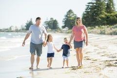 Jeune père heureux et beau de mère de famille tenant la main de la marche de fils et de fille joyeuse sur la plage appréciant le  Image stock