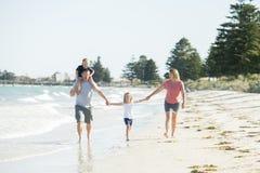 Jeune père heureux et beau de mère de famille tenant la main de la marche de fils et de fille joyeuse sur la plage appréciant le  Photo stock