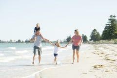 Jeune père heureux et beau de mère de famille tenant la main de la marche de fils et de fille joyeuse sur la plage appréciant le  Photographie stock