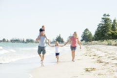 Jeune père heureux et beau de mère de famille tenant la main de la marche de fils et de fille joyeuse sur la plage appréciant le  Image libre de droits