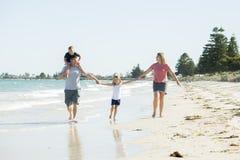 Jeune père heureux et beau de mère de famille tenant la main de la marche de fils et de fille joyeuse sur la plage appréciant le  Images libres de droits