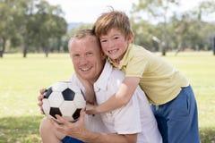 Jeune père heureux et 7 ou 8 années excitées de fils jouant ensemble le football du football sur le jardin de parc de ville posan Image stock