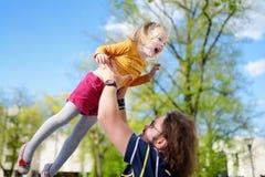 Jeune père heureux tenant sa petite fille le jour d'été photographie stock libre de droits