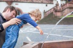 Jeune père jouant avec le garçon d'enfant en bas âge avec de l'eau de fontaine Images libres de droits