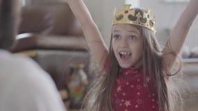 Jeune père mettant la couronne sur la tête de sa petite fille, composant sa princesse étroite La fille est heureuse, elle clips vidéos