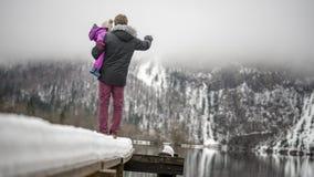 Jeune père se tenant sur l'extrémité d'un pilier neigeux dans un holdi de lac Images stock