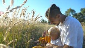 Jeune père tenant l'épillet disponible et jouant avec l'enfant au pré Famille heureuse s'asseyant à l'herbe et ayant l'amusement  clips vidéos