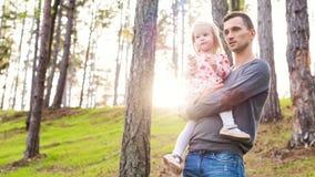 Jeune père tenant la fille mignonne d'enfant en bas âge dans son bras tandis que sur une promenade dans une forêt Images stock