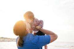Jeune père tenant son enfant sur la plage et les baisers Photographie stock