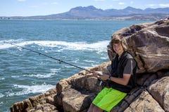 Jeune pêche d'adolescent par la mer Image libre de droits