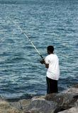Jeune pêche d'homme de couleur Photographie stock libre de droits