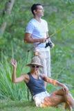 Jeune pêche de couples sur l'étang de banques Photo stock