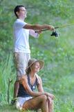 Jeune pêche de couples sur l'étang de banques Images libres de droits