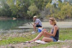 Jeune pêche de couples sur l'étang de banques Images stock