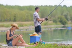 Jeune pêche de couples sur l'étang de banques Photographie stock libre de droits